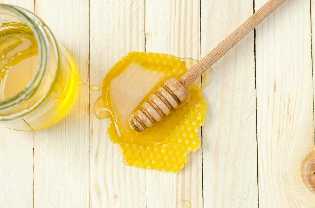 A jar of honey and a honey spoon.